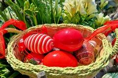 Καλάθι Πάσχας με τα κόκκινα χρωματισμένα αυγά και τα διαφορετικά σχέδια στοκ φωτογραφία
