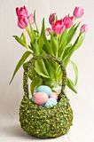 Καλάθι Πάσχας των χρωματισμένων αυγών και ομάδα άνοιξη tulilps στοκ φωτογραφίες