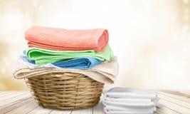 Καλάθι πλυντηρίων με τις ζωηρόχρωμες πετσέτες σε ξύλινο Στοκ Φωτογραφίες