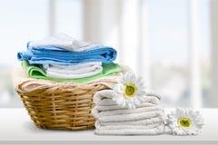 Καλάθι πλυντηρίων με τις ζωηρόχρωμες πετσέτες στο υπόβαθρο Στοκ φωτογραφία με δικαίωμα ελεύθερης χρήσης