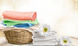 Καλάθι πλυντηρίων με τις ζωηρόχρωμες πετσέτες στο υπόβαθρο Στοκ Φωτογραφία