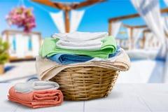 Καλάθι πλυντηρίων με τις ζωηρόχρωμες πετσέτες στο υπόβαθρο Στοκ φωτογραφίες με δικαίωμα ελεύθερης χρήσης