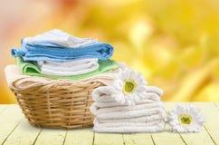 Καλάθι πλυντηρίων με τις ζωηρόχρωμες πετσέτες στο υπόβαθρο Στοκ Φωτογραφίες