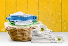 Καλάθι πλυντηρίων με τις ζωηρόχρωμες πετσέτες στο υπόβαθρο Στοκ Εικόνα