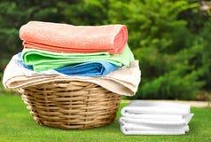 Καλάθι πλυντηρίων με τις ζωηρόχρωμες πετσέτες στο υπόβαθρο Στοκ Εικόνες