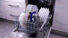 Καλάθι πλυντηρίων πιάτων με τα βρώμικα άσπρα πιάτα και μαχαιροπήρουνα στην κουζίνα απόθεμα βίντεο