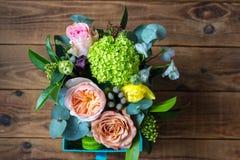 Καλάθι των λουλουδιών και εύγευστα macaroons επιδορπίων σε ένα ξύλινο υπόβαθρο στοκ εικόνες