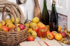 Καλάθι των μήλων, μπουκάλια του μηλίτη και του παλαιού σημειωματάριου Στοκ Φωτογραφίες