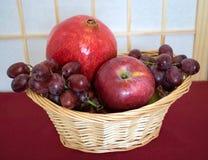 Καλάθι φρούτων με τη Apple, τα σταφύλια και ένα ρόδι Στοκ Φωτογραφίες