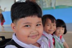 Καλά παχιά κορίτσια στην αγροτική περιοχή που φορούν τη σχολική στολή, σχολική τσάντα Καθίστε στην ξύλινη καρέκλα και το χαμόγελο στοκ εικόνες