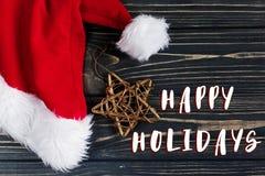 Καλές διακοπές σημάδι κειμένων στο χρυσά αστέρι Χριστουγέννων και το καπέλο santa Στοκ εικόνα με δικαίωμα ελεύθερης χρήσης
