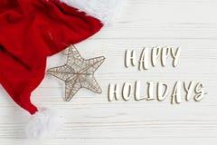 Καλές διακοπές σημάδι κειμένων στο χρυσά αστέρι Χριστουγέννων και το καπέλο santa Στοκ φωτογραφία με δικαίωμα ελεύθερης χρήσης