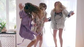 Καλές διακοπές, τα λεπτά κορίτσια πηδούν τη διασκέδαση στο κρεβάτι κατά τη διάρκεια του κόμματος πυτζαμών σε σε αργή κίνηση φιλμ μικρού μήκους