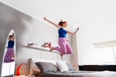 Καλές ειδήσεις για το ευτυχές νέο άλμα κοριτσιών γυναικών στο κρεβάτι Στοκ φωτογραφία με δικαίωμα ελεύθερης χρήσης