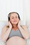 Καλή έγκυος γυναίκα που ακούει τη μουσική Στοκ φωτογραφία με δικαίωμα ελεύθερης χρήσης