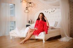 Καλή έγκυος γυναίκα στη ρόδινη συνεδρίαση ρομπών στο κρεβάτι Στοκ Φωτογραφία