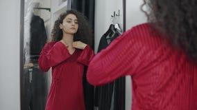 Καλή γυναίκα που εξετάζει την σε έναν καθρέφτη σε ένα κατάστημα απόθεμα βίντεο