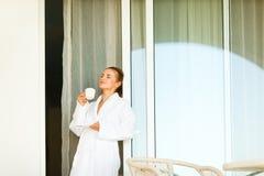 Καλή γυναίκα στο μπουρνούζι που στέκεται κοντά στα μεγάλα Windows Στοκ Εικόνες