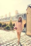 Καλή γυναίκα brunette με την κυματίζοντας τρίχα που φορά το καθιερώνον τη μόδα φόρεμα, Στοκ Εικόνα