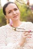 Καλή γυναίκα brunette με τη φυσική τοποθέτηση makeup κοντά στο bloomi Στοκ Εικόνες