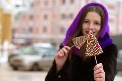 Καλή γυναίκα brunette στο πορφυρό μαντίλι που κρατά τα ζωηρόχρωμα Χριστούγεννα Στοκ εικόνες με δικαίωμα ελεύθερης χρήσης