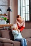 Καλή κυρία νέος-ενηλίκων που βάζει μαλακά το χέρι στον ώμο μητέρων στοκ εικόνα