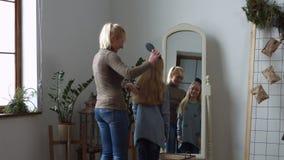 Καλή μητέρα που κτενίζει την τρίχα κορών της ` s στο σπίτι απόθεμα βίντεο
