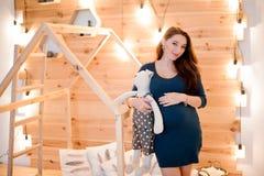 Καλή νέα έγκυος γυναίκα που στέκεται στο υπόβαθρο του ξύλινου τοίχου Στοκ Φωτογραφία