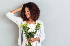 Καλή νέα αφρικανική ανθοδέσμη και χαμόγελο λουλουδιών εκμετάλλευσης γυναικών Στοκ Εικόνες