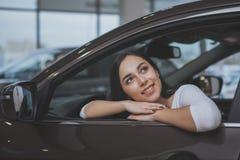 Καλή νέα γυναίκα που αγοράζει το νέο αυτοκίνητο στον αντιπρόσωπο στοκ εικόνες με δικαίωμα ελεύθερης χρήσης