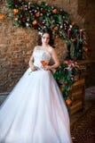 Καλή νύφη σε ένα μακρύ άσπρο φόρεμα που κρατά ένα λουλούδι στοκ φωτογραφία με δικαίωμα ελεύθερης χρήσης