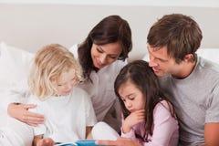 Καλή οικογένεια που διαβάζει ένα βιβλίο Στοκ Εικόνες