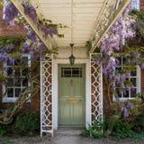 Καλή πόρτα που περιβάλλεται από τις εγκαταστάσεις και τα όμορφα λουλούδια στοκ εικόνα