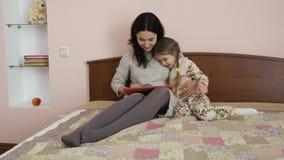 Καλή συνεδρίαση ταμπλετών χρήσεων μητέρων και κορών στο κρεβάτι στο σπίτι φιλμ μικρού μήκους
