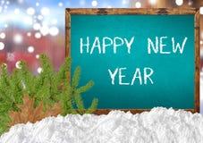 Καλή χρονιά στον μπλε πίνακα με το πεύκο και το χιόνι πόλεων blurr Στοκ Εικόνες