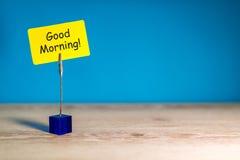 Καλημέρα - επιθυμία για μια καλημέρα Σημείωση στο κίτρινο έγγραφο στο μπλε υπόβαθρο Με το κενό διάστημα για το κείμενο, πρότυπο κ στοκ φωτογραφία με δικαίωμα ελεύθερης χρήσης