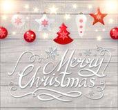Καλλιγραφική εγγραφή Χαρούμενα Χριστούγεννας στο κομψό μαλακό ξύλινο κατασκευασμένο υπόβαθρο με τα χρυσά φω'τα και τα παιχνίδια Χ Στοκ φωτογραφία με δικαίωμα ελεύθερης χρήσης