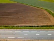 Καλλιεργήσιμο έδαφος άνοιξη Ένας τομέας και ένας δρόμος επάνω από την όψη Στοκ φωτογραφία με δικαίωμα ελεύθερης χρήσης