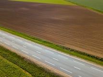 Καλλιεργήσιμο έδαφος άνοιξη Ένας τομέας και ένας δρόμος επάνω από την όψη Στοκ Φωτογραφία
