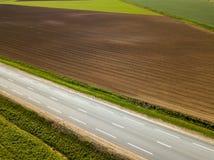 Καλλιεργήσιμο έδαφος άνοιξη Ένας τομέας και ένας δρόμος επάνω από την όψη Στοκ Φωτογραφίες
