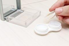 Καλλιεργημένα θηλυκά χέρια που παίρνουν τους φακούς επαφής από ένα εμπορευματοκιβώτιο στοκ εικόνα με δικαίωμα ελεύθερης χρήσης