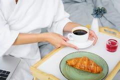 καλλιεργημένη άποψη της γυναίκας στο μπουρνούζι που έχει το πρόγευμα με τον καφέ στοκ εικόνα