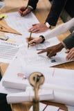 καλλιεργημένη άποψη των multiethnic αρχιτεκτόνων που συζητούν τα έγγραφα και που σύρουν τα σχεδιαγράμματα στοκ εικόνες
