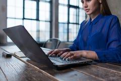 Καλλιεργημένη εικόνα της νέας γυναίκας υπάλληλος που εργάζεται στο κείμενο δακτυλογράφησης προγράμματος στο lap-top στο εσωτερικό στοκ εικόνα