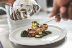 καλλιεργημένη εικόνα του αρχιμάγειρα αφροαμερικάνων που διακοσμεί το πιάτο με τα τρόφιμα στοκ φωτογραφία