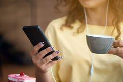 Καλλιεργημένη μπροστινή άποψη του καφέ κατανάλωσης κοριτσιών, ακούοντας τη μουσική, που τρώει το κέικ στοκ εικόνες