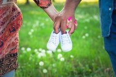 Καλλιεργημένη πυροβοληθείσα άποψη της αναμονής των γονέων που κρατούν τα παπούτσια μωρών Εγκυμοσύνη, μητρότητα και νέα οικογενεια στοκ εικόνες