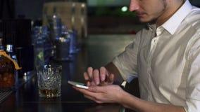 Καλλιεργημένος κοντά επάνω ενός ατόμου που χρησιμοποιεί το έξυπνο τηλέφωνό του στο φραγμό ενώ έχοντας ένα ποτό απόθεμα βίντεο