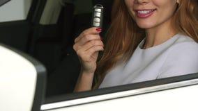 Καλλιεργημένος κοντά επάνω ενός εύθυμου θηλυκού οδηγού που παρουσιάζει αυτοκίνητο κλειδώνει το κάθισμα σε ένα αυτοκίνητο φιλμ μικρού μήκους