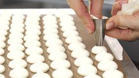 Καλλιεργημένος κοντά επάνω ενός ζαχαροπλάστη που χρησιμοποιεί την τσάντα ζύμης που προετοιμάζει τα μπισκότα μαρέγκας απόθεμα βίντεο